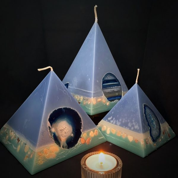 Our Patchouli and Sandalwood nest of pyramids combined burn time is over 440 hours. As your pyramid candle burns, the flame illuminates the Agate, revealing the stone's unique variegated patterns, and leaves you with a gorgeous keepsake. Essential oils of Himalayan Patchouli and Sandalwood create a sophisticated scent reminiscent of the swinging 60s' counter-culture. A crisp ribbon of white separating the navy body from its teal base is embedded with river pebbles.