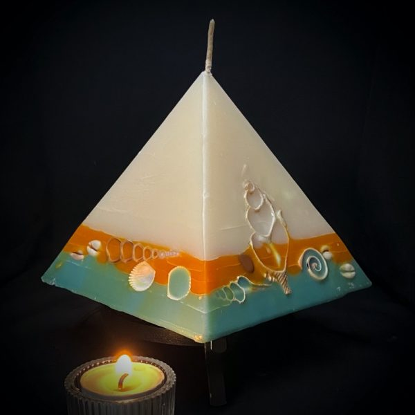 Nefertiti: mid size in our pyramid range burning over 150 hours. Take me to the beach please! Fresh, warm and tropically scented this range is infused with essential oils of lime and coconut. White in colour, these candles feature an sunburnt orange and teal banded base embedded with sea shells. As you near the end of your candle's burning, the trove of exotic shells is revealed - your lasting keepsake.