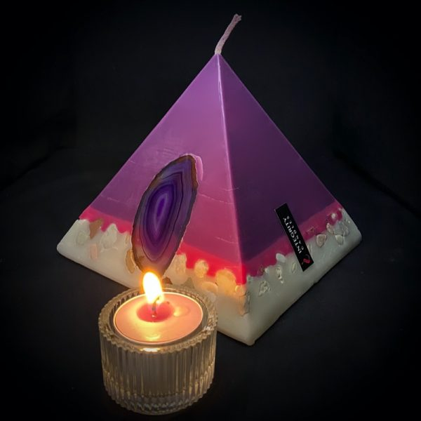 Nefertiti: mid size in our pyramid range and burning over 140 hours. Deeply relaxing, essential oils of Lavender, Patchouli, Citrus, Marjoram, Jojoba, Geranium and Chamomile are presented in a meditative shade of purple. A band of magenta sits above a white base embedded with agate slices and river pebble. As your pyramid candle burns, the flame illuminates the Agate slice, revealing the stone's unique variegated pattern, and leaves you with gorgeous keepsakes.