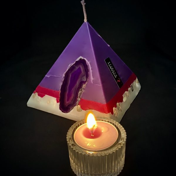 Tutankhamon: smallest in our pyramid range and burning over 90 hours. Deeply relaxing, essential oils of Lavender, Patchouli, Citrus, Marjoram, Jojoba, Geranium and Chamomile are presented in a meditative shade of purple. A band of magenta sits above a white base embedded with river pebble. As your pyramid candle burns, the flame illuminates an Agate slice, revealing the stone's unique variegated pattern, and leaves you with gorgeous keepsake.